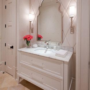 На фото: маленький туалет в стиле современная классика с врезной раковиной, фасадами с утопленной филенкой, белыми фасадами, мраморной столешницей, белыми стенами, полом из известняка и бежевой плиткой с