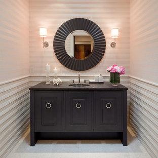 На фото: маленький туалет в стиле современная классика с врезной раковиной, фасадами островного типа, темными деревянными фасадами, столешницей из гранита, бежевой плиткой, каменной плиткой, белыми стенами, полом из известняка и черной столешницей