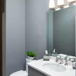 Inspiration for a small timeless powder room remodel in Birmingham with recessed-panel cabinets, gray cabinets, a two-piece toilet, gray walls, an undermount sink and quartz countertops