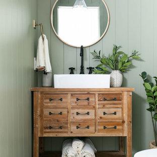 Exemple d'un WC et toilettes nature avec un placard en trompe-l'oeil, des portes de placard en bois brun, un mur vert, une vasque, un sol gris et un plan de toilette marron.