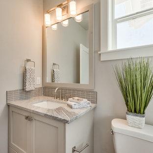 Cette photo montre un WC et toilettes moderne de taille moyenne avec un placard avec porte à panneau encastré, des portes de placard blanches, un WC séparé, un carrelage gris, des carreaux de céramique, un mur gris, un lavabo encastré, un plan de toilette en calcaire et un plan de toilette gris.
