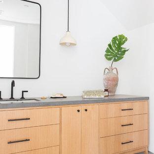 Idées déco pour un WC et toilettes moderne avec un placard à porte plane, des portes de placard en bois clair, un mur blanc, béton au sol, un lavabo encastré, un sol gris et un plan de toilette gris.