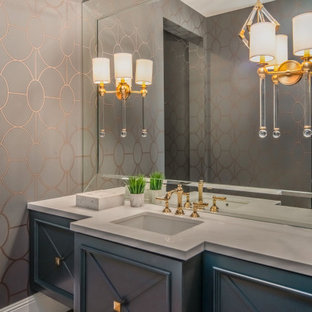 Inspiration for a mediterranean powder room remodel in Phoenix with recessed-panel cabinets, blue cabinets, multicolored walls, an undermount sink and white countertops