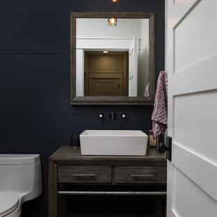 Idée de décoration pour un WC et toilettes champêtre avec un placard à porte plane, des portes de placard grises, un mur bleu, un sol en bois brun, une vasque, un plan de toilette en bois, un sol marron et un plan de toilette gris.