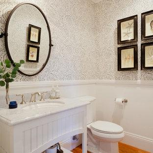 Modelo de aseo tradicional, pequeño, con armarios con rebordes decorativos, puertas de armario blancas, sanitario de dos piezas, suelo de madera en tonos medios, lavabo bajoencimera y encimera de mármol
