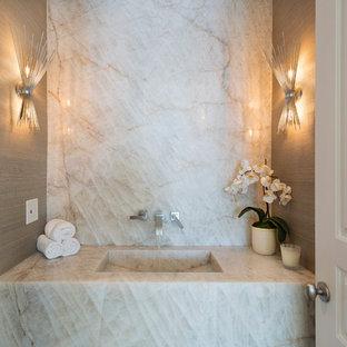 Свежая идея для дизайна: туалет среднего размера в морском стиле с коричневыми стенами, монолитной раковиной, мраморной столешницей, бежевой плиткой, плиткой из листового камня и бежевой столешницей - отличное фото интерьера