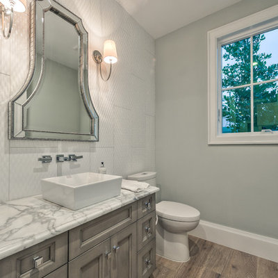 Small gray tile and cement tile light wood floor and brown floor powder room photo with recessed-panel cabinets, gray cabinets, a two-piece toilet, gray walls, a vessel sink and granite countertops