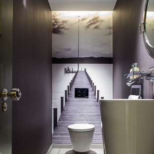 Photo of a medium sized contemporary cloakroom in London with a pedestal sink, a wall mounted toilet and purple walls.