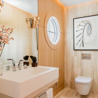 ボストンのコンテンポラリースタイルのおしゃれなトイレ・洗面所 (壁掛け式トイレ、ベージュのタイル、壁付け型シンク、トラバーチンタイル、ベージュの床) の写真