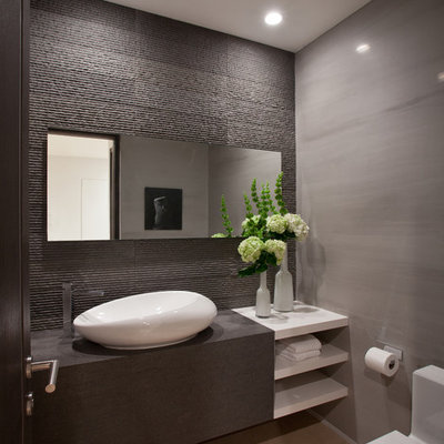 Example of a mid-sized trendy gray tile ceramic tile and beige floor powder room design in Miami with a vessel sink, open cabinets, white cabinets, wood countertops, a one-piece toilet, gray walls and gray countertops