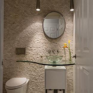 Пример оригинального дизайна интерьера: маленький туалет в стиле модернизм с плоскими фасадами, белыми фасадами, унитазом-моноблоком, бежевой плиткой, каменной плиткой, бежевыми стенами, полом из мозаичной плитки, настольной раковиной, стеклянной столешницей и бежевым полом