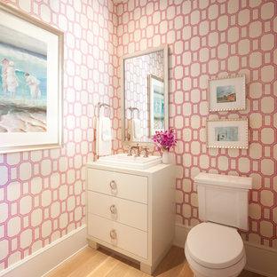 Kleine Klassische Gästetoilette mit flächenbündigen Schrankfronten, weißen Schränken, rosa Wandfarbe, hellem Holzboden, Wandtoilette mit Spülkasten und Aufsatzwaschbecken in Minneapolis