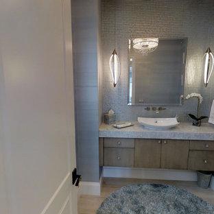 На фото: туалет среднего размера в стиле современная классика с плоскими фасадами, серыми фасадами, унитазом-моноблоком, серой плиткой, стеклянной плиткой, серыми стенами, полом из керамической плитки, настольной раковиной, столешницей из кварцита и бежевым полом с
