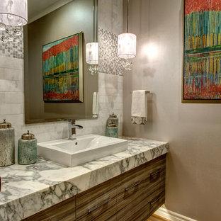 На фото: маленький туалет в стиле современная классика с плоскими фасадами, фасадами цвета дерева среднего тона, мраморной столешницей, унитазом-моноблоком, белой плиткой, каменной плиткой, серыми стенами, паркетным полом среднего тона и накладной раковиной с