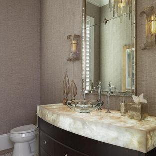 Стильный дизайн: туалет среднего размера в средиземноморском стиле с плоскими фасадами, коричневыми фасадами, унитазом-моноблоком, коричневыми стенами, полом из керамической плитки, настольной раковиной, столешницей из оникса, разноцветным полом и разноцветной столешницей - последний тренд