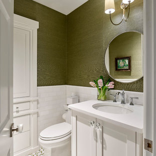 フィラデルフィアの中くらいのトランジショナルスタイルのおしゃれなトイレ・洗面所 (白いキャビネット、一体型トイレ、白いタイル、セラミックタイル、緑の壁、モザイクタイル、アンダーカウンター洗面器、人工大理石カウンター、白い洗面カウンター、シェーカースタイル扉のキャビネット、マルチカラーの床) の写真