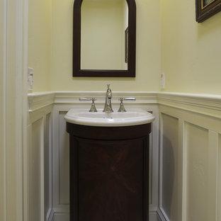 Exemple d'un WC et toilettes craftsman avec un lavabo posé, un placard en trompe-l'oeil et des portes de placard en bois sombre.