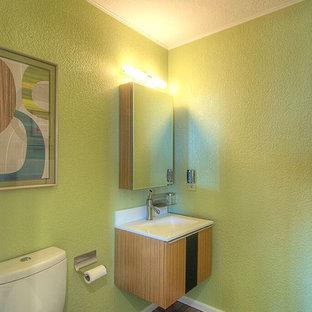Idées déco pour un petit WC et toilettes contemporain avec un placard à porte plane, des portes de placard marrons, un mur vert, un sol en liège et un lavabo intégré.