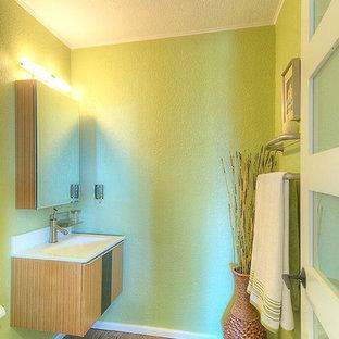 Exemple d'un petit WC et toilettes tendance avec un placard à porte plane, des portes de placard marrons, un mur vert, un sol en liège et un lavabo intégré.