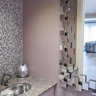 Imagen de aseo actual, pequeño, con armarios con paneles lisos, puertas de armario violetas, sanitario de una pieza, baldosas y/o azulejos multicolor, baldosas y/o azulejos en mosaico, paredes púrpuras, suelo de madera en tonos medios, lavabo bajoencimera, encimera de terrazo y suelo gris