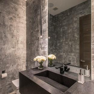Стильный дизайн: большой туалет в современном стиле с плоскими фасадами, черными фасадами, инсталляцией, серой плиткой, полом из керамогранита, монолитной раковиной, серым полом, черной столешницей и подвесной тумбой - последний тренд