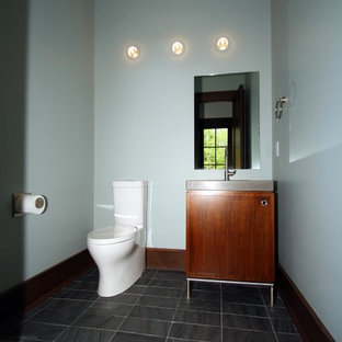 Inspiration for a small traditional cloakroom in Indianapolis with a wall mounted toilet, blue walls, flat-panel cabinets, medium wood cabinets, slate flooring, an integrated sink, engineered stone worktops and grey floors.