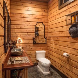 Mittelgroße Urige Gästetoilette mit verzierten Schränken, hellbraunen Holzschränken, Toilette mit Aufsatzspülkasten, brauner Wandfarbe, Betonboden, Aufsatzwaschbecken und Waschtisch aus Holz in Philadelphia