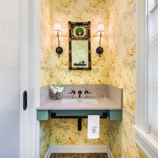 Lantlig inredning av ett litet toalett, med en toalettstol med hel cisternkåpa, beige kakel, gula väggar, mosaikgolv, ett undermonterad handfat och bänkskiva i kvarts