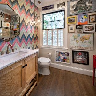 Kleine Klassische Gästetoilette mit braunem Holzboden, Unterbauwaschbecken, Quarzwerkstein-Waschtisch, braunem Boden, weißer Waschtischplatte, verzierten Schränken, hellen Holzschränken und bunten Wänden in Washington, D.C.