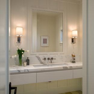 Esempio di un bagno di servizio chic con ante lisce, ante bianche, pareti bianche, parquet chiaro, lavabo sottopiano, top in marmo e top bianco