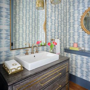 Пример оригинального дизайна: туалет в стиле современная классика с плоскими фасадами, серыми фасадами, синими стенами, паркетным полом среднего тона, настольной раковиной, коричневым полом, серой столешницей, напольной тумбой и обоями на стенах