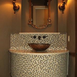 На фото: с высоким бюджетом большие туалеты в средиземноморском стиле с унитазом-моноблоком, бежевой плиткой, плиткой из листового стекла, коричневыми стенами, темным паркетным полом, настольной раковиной и столешницей из гранита