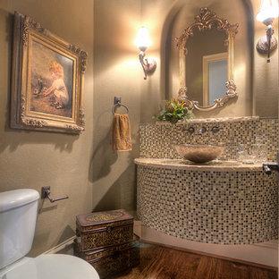 Exemple d'un grand WC et toilettes méditerranéen avec un WC à poser, un carrelage marron, des plaques de verre, un mur beige, un sol en bois brun, une vasque et un plan de toilette en granite.
