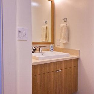 Idées déco pour un petit WC et toilettes contemporain avec un mur blanc, un sol en bambou, un lavabo posé, un sol marron, un placard à porte plane, des portes de placard en bois brun, un WC séparé et un plan de toilette beige.