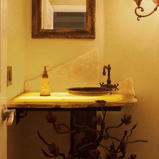 Пример оригинального дизайна: маленький туалет в современном стиле с раздельным унитазом, серой плиткой, каменной плиткой, бежевыми стенами, настольной раковиной и столешницей из известняка