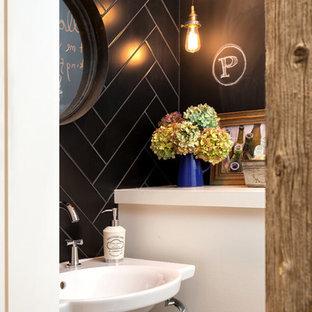 Пример оригинального дизайна: маленький туалет в стиле лофт с подвесной раковиной, черной плиткой, керамогранитной плиткой и черными стенами