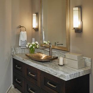 Cette image montre un petit WC et toilettes traditionnel avec un placard à porte shaker, des portes de placard en bois sombre, un mur gris, un sol en carrelage de porcelaine, une vasque, un plan de toilette en granite et un plan de toilette gris.