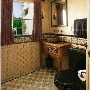 Идея дизайна: маленький туалет в средиземноморском стиле с фасадами островного типа, фасадами цвета дерева среднего тона, раздельным унитазом, разноцветной плиткой, керамической плиткой, желтыми стенами, полом из керамической плитки, настольной раковиной и столешницей из дерева