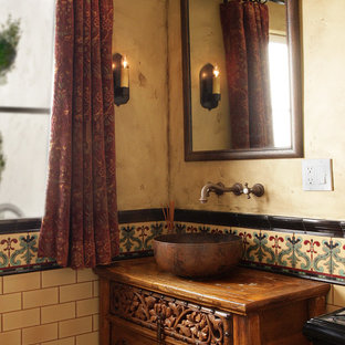 Small mediterranean cloakroom in Los Angeles with freestanding cabinets, medium wood cabinets, a two-piece toilet, multi-coloured tiles, ceramic tiles, a vessel sink, wooden worktops, beige walls and brown worktops.