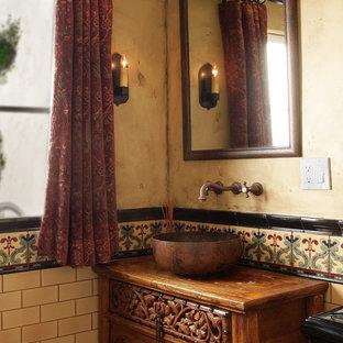 Cette image montre un petit WC et toilettes méditerranéen avec un placard en trompe-l'oeil, des portes de placard en bois brun, un WC séparé, un carrelage multicolore, des carreaux de céramique, une vasque, un plan de toilette en bois, un mur beige et un plan de toilette marron.