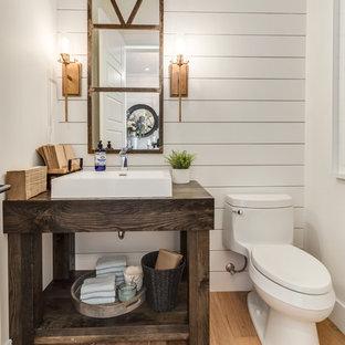 Идея дизайна: туалет среднего размера в стиле кантри с открытыми фасадами, темными деревянными фасадами, унитазом-моноблоком, белыми стенами, светлым паркетным полом, настольной раковиной, столешницей из дерева, бежевым полом и коричневой столешницей