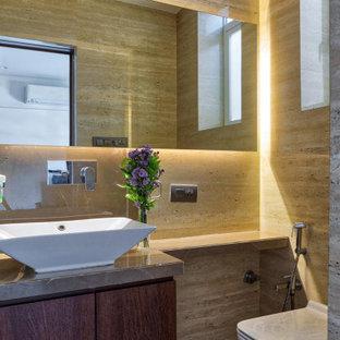 Esempio di un bagno di servizio minimal con ante lisce, ante in legno scuro, WC sospeso, piastrelle beige, piastrelle marroni, lavabo a bacinella, pavimento beige e top marrone