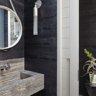 На фото: туалет в морском стиле с черными стенами, подвесной раковиной, полом из травертина, столешницей из травертина, черным полом и черной столешницей с