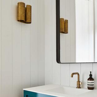 Cette photo montre un WC et toilettes bord de mer avec des portes de placard turquoises, un mur blanc, un lavabo intégré et un plan de toilette blanc.