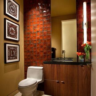 Diseño de aseo de estilo americano con lavabo bajoencimera, armarios con paneles lisos, puertas de armario de madera en tonos medios, baldosas y/o azulejos naranja y sanitario de una pieza