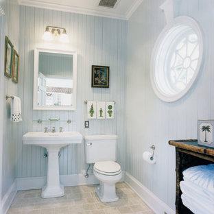 Foto de aseo clásico con lavabo con pedestal, paredes azules y suelo de travertino