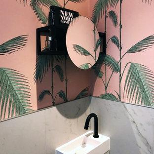 Cette photo montre un petit WC et toilettes moderne avec un WC suspendu, un carrelage blanc, des carreaux de céramique, un mur rose, un sol en carrelage de céramique, un lavabo suspendu et un sol blanc.