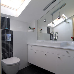Powder room - contemporary black tile black floor powder room idea in Tel Aviv with a vessel sink, flat-panel cabinets, white cabinets and a wall-mount toilet