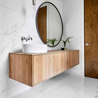 Idées déco pour un grand WC et toilettes contemporain avec un placard à porte plane, des portes de placard en bois clair, un carrelage blanc, du carrelage en marbre, un mur blanc, un sol en marbre, une vasque, un plan de toilette en bois, un sol blanc et un plan de toilette beige.