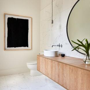 Große Moderne Gästetoilette mit flächenbündigen Schrankfronten, hellen Holzschränken, weißen Fliesen, Marmorfliesen, weißer Wandfarbe, Marmorboden, Aufsatzwaschbecken, Waschtisch aus Holz, weißem Boden und beiger Waschtischplatte in Charlotte